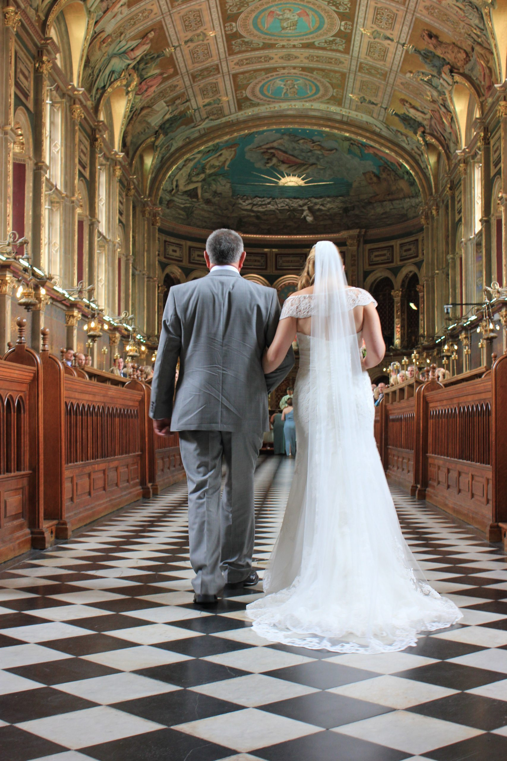 Bride& her dad walking down the aisle of a church with a black & white chequered floor.
