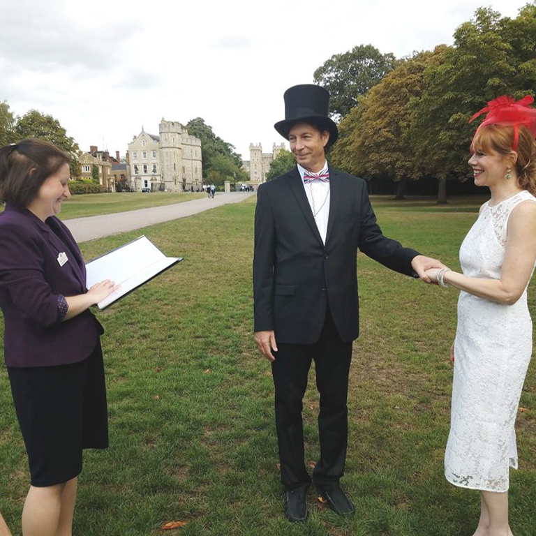 Lady wearing a purple jacket holding a folder looks towards a lady wearing a white dress and a man wearing a suit and a top hat with a union jack bow tie.