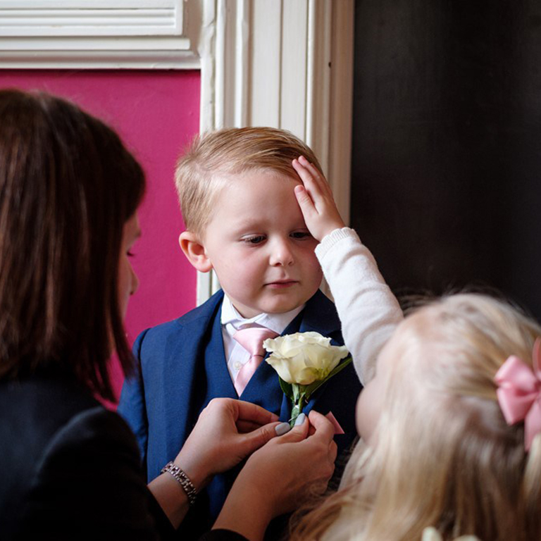 A lady with dark hair attaches a buttonwhole to the jacket of a small boy as a blond haired girl places her hand on his forehead.