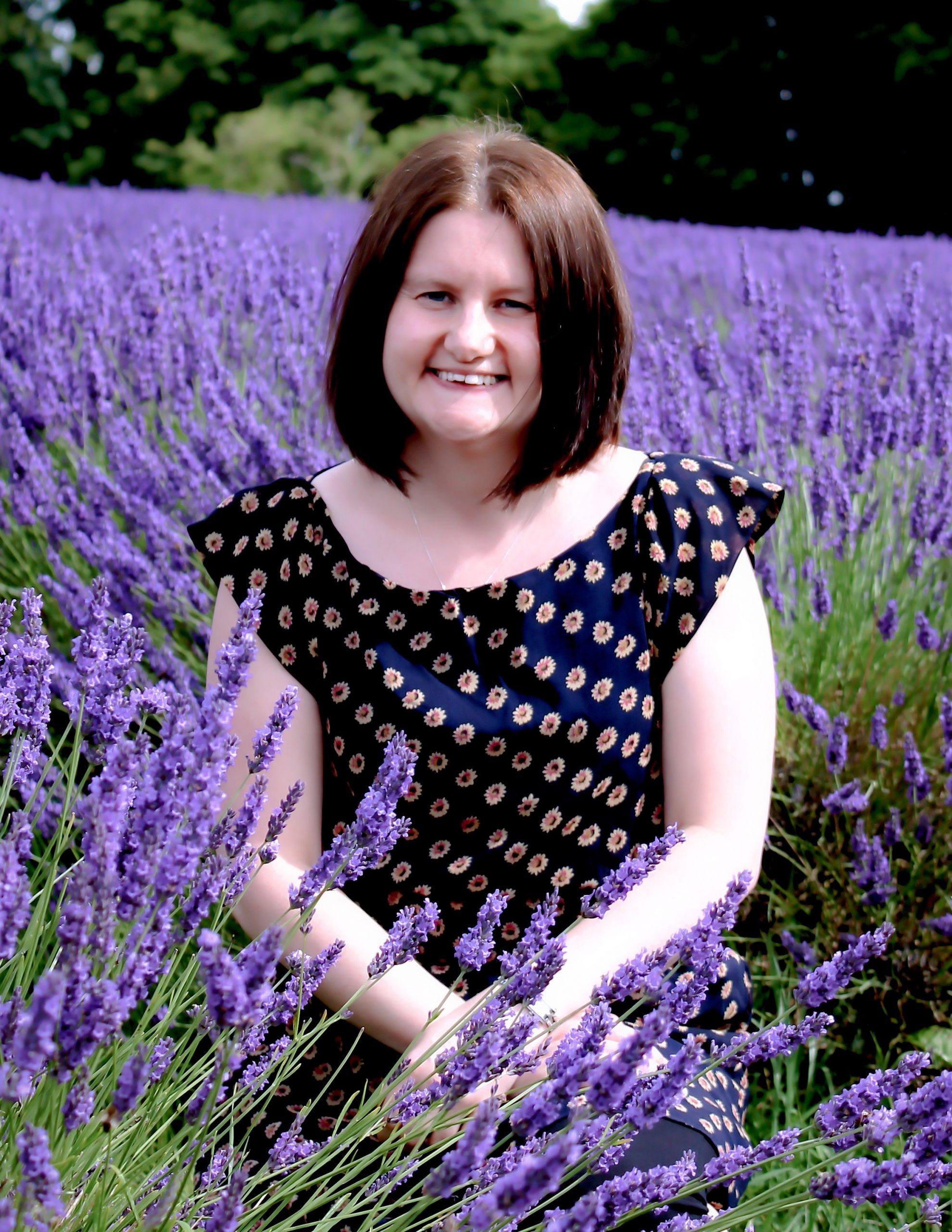 Samantha dobson wearing a navey dress with sunflowers on, sitting in a lavender field.