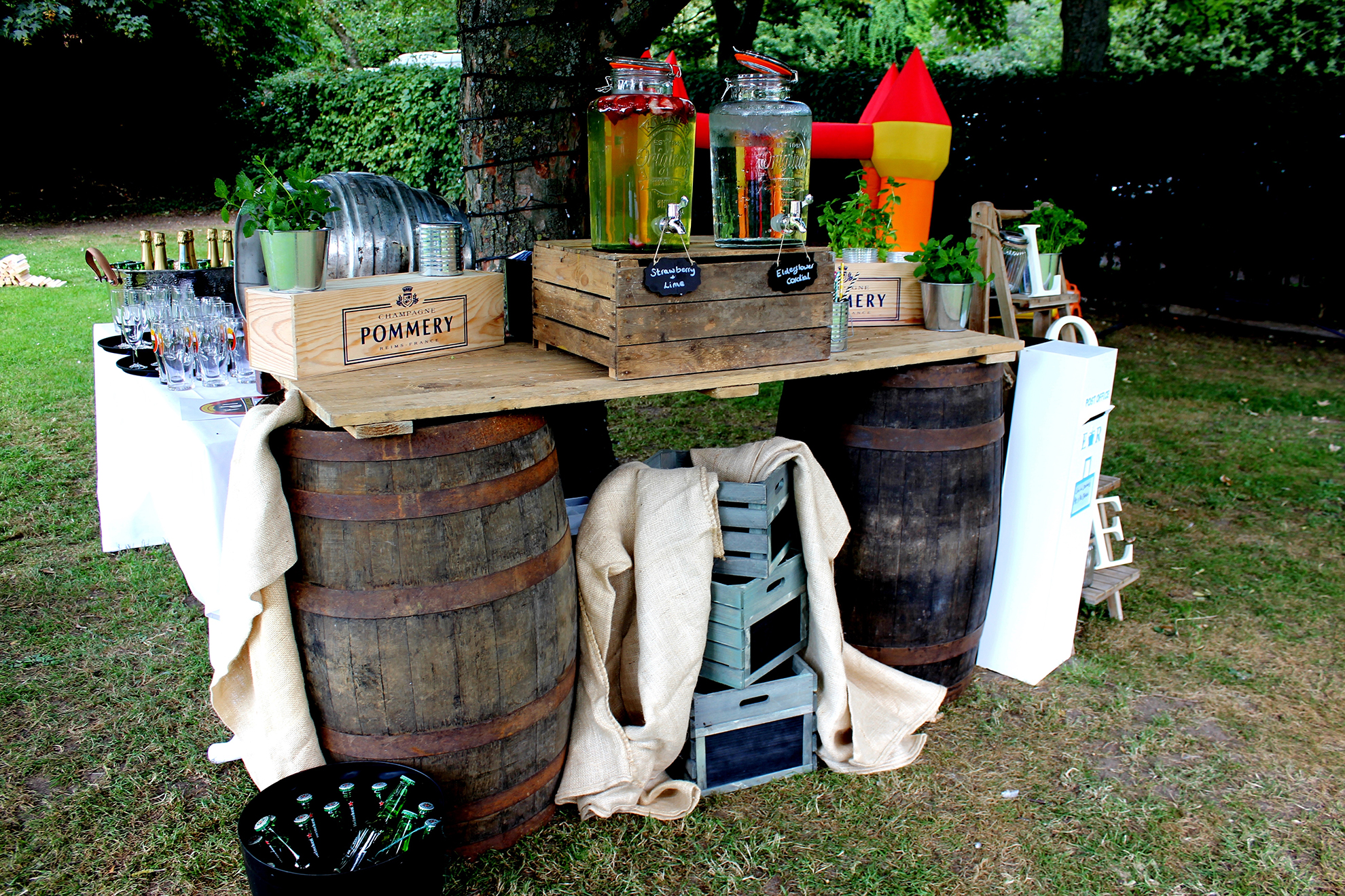A diy bar set up made out of two barrels with a door as the bar top. Ontop of the bar there are various boxes with two kilner jars containing elderflower cordial and strawberry & lime cordial. there are champagne flutes and champagne and a red & yellow bouncy castle.