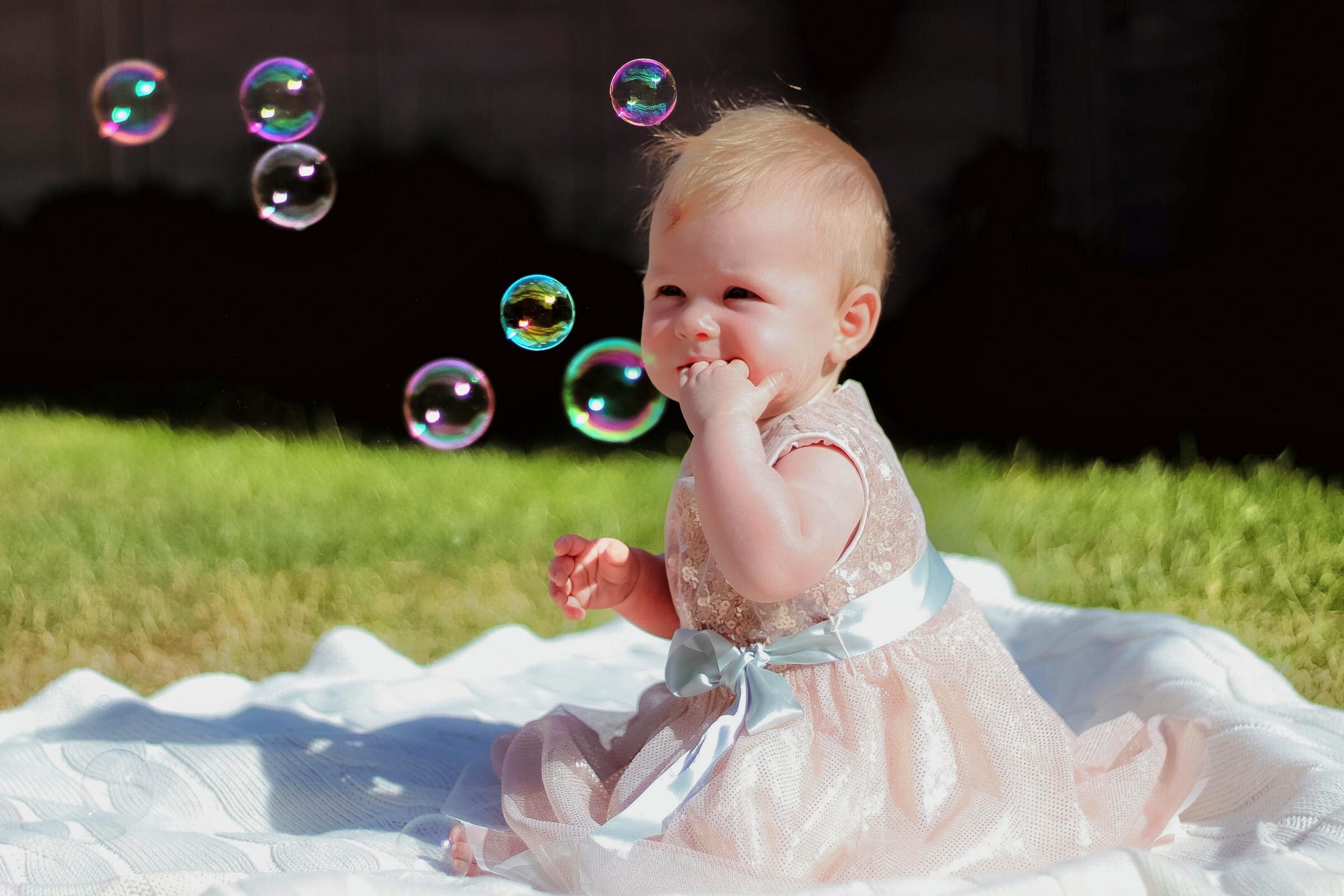 Baby girl sitting on a mat wearing a pink dress with a hand in her mouth watching bubbles