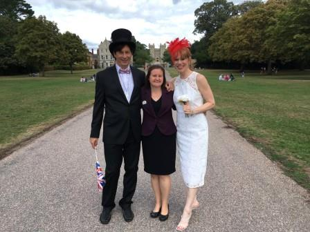A tall man wearing a black suit and a top hat with a union jack bow tie stands on a path infront of windsor castel with his arm around a small woman wearing a green dress and a balck jacket. She has her arm around a tall lady wearing a white dress.