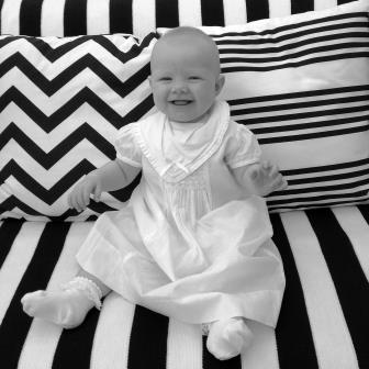 Baby wearing white sitting on a black and white sofa