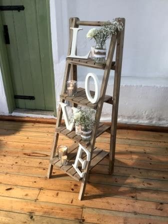 A wooden ladder has the letters LOVE to different steps. There are small jars of flowers on the steps.