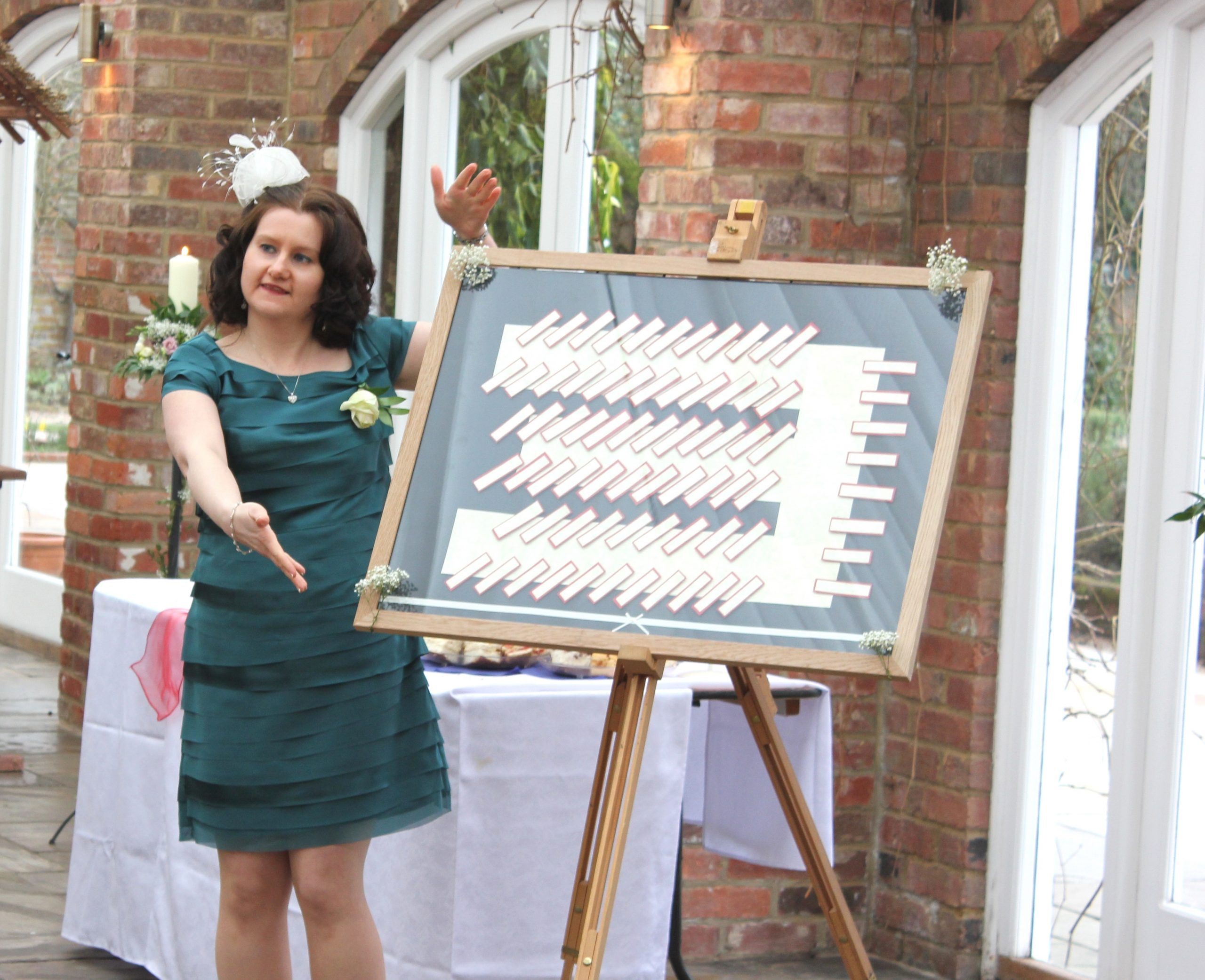 A lady in a green dress draws the attention of the wedding guests to the tableplan.