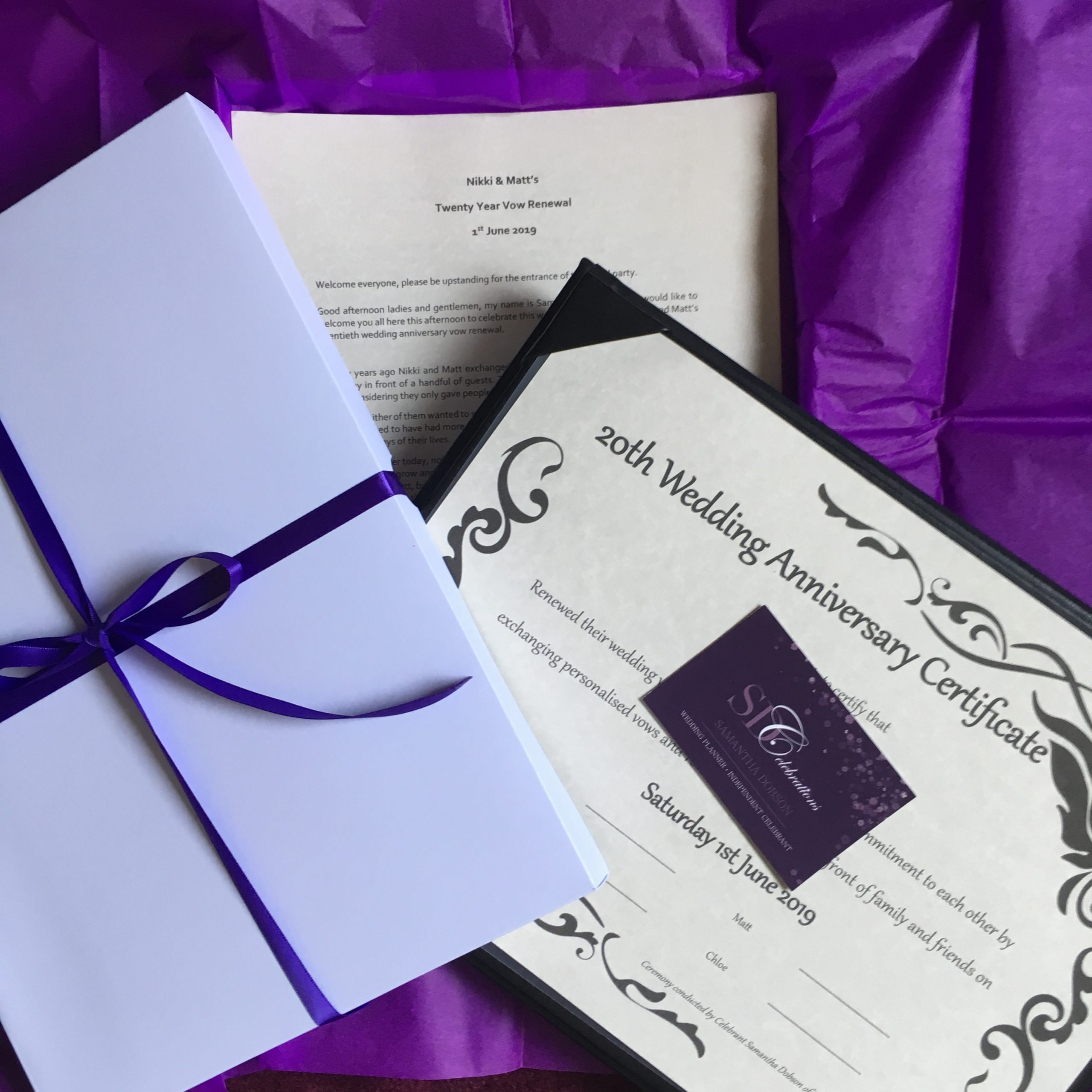 The script for a 20 year vow renewal ceremony is under a 20th Wedding Anniversary Certificate with a business card for SDCelebrations on the top. The lid for the presentation box is on the left.