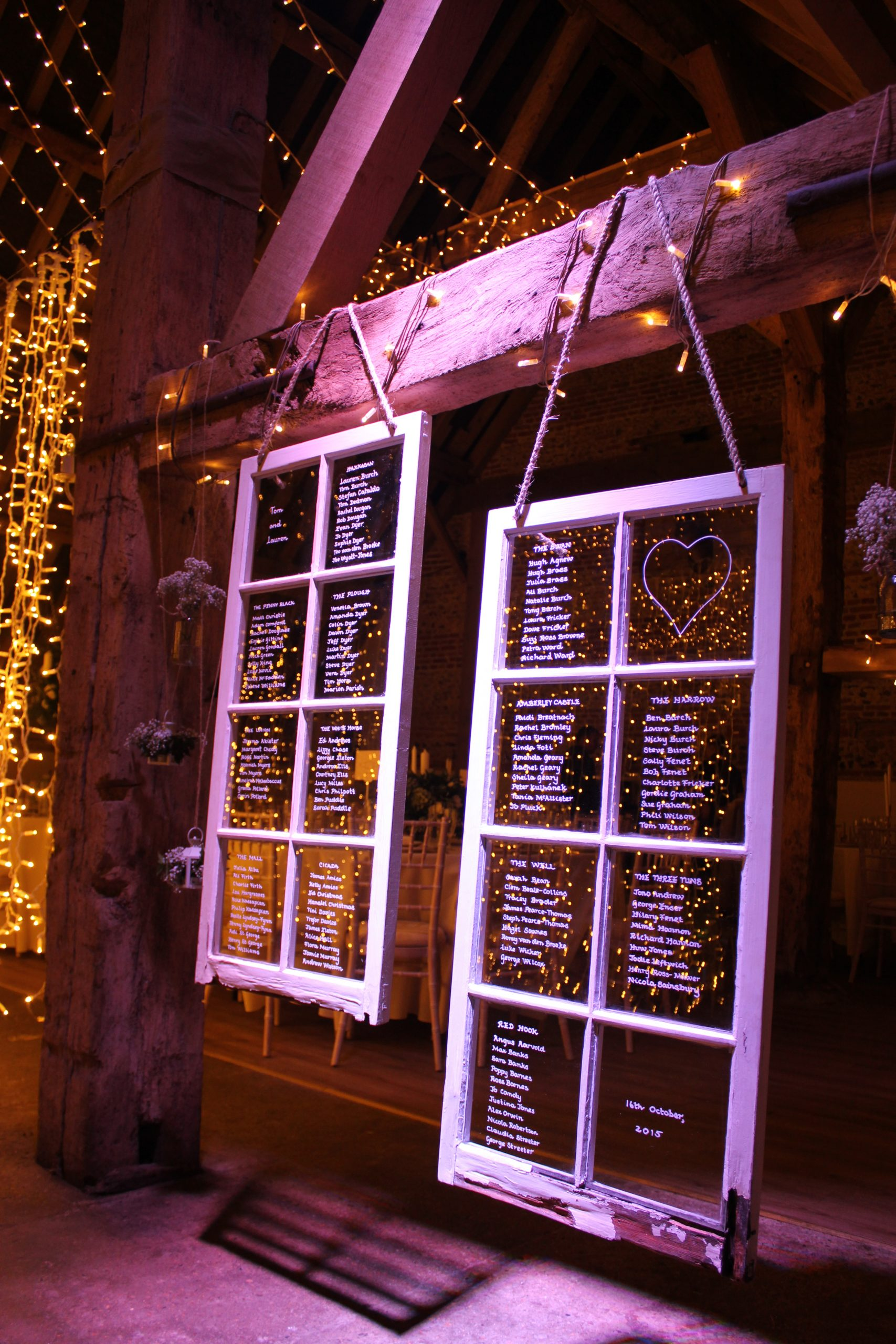 Two window frames with a wedding tableplan written on them hanging from the beam of a barn ceiling. There are strings of fairy ligts around.