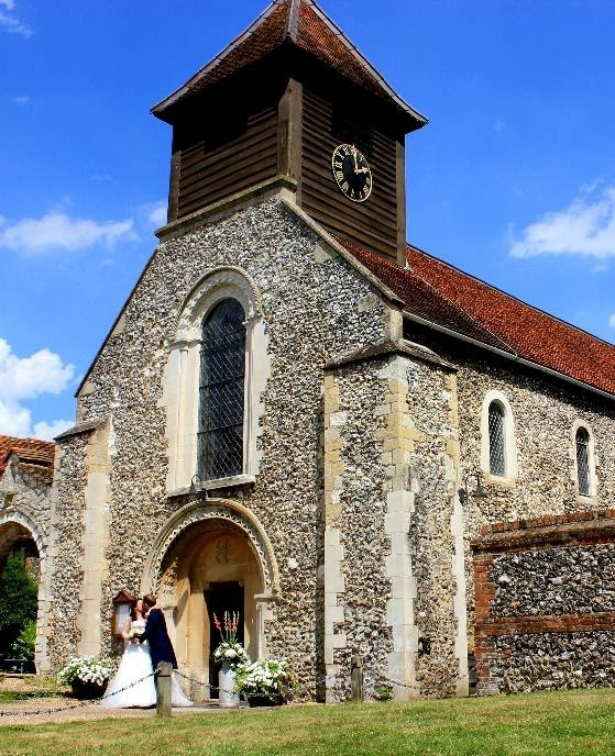 A bride and groom kiss outside a brick church with a blue sky.