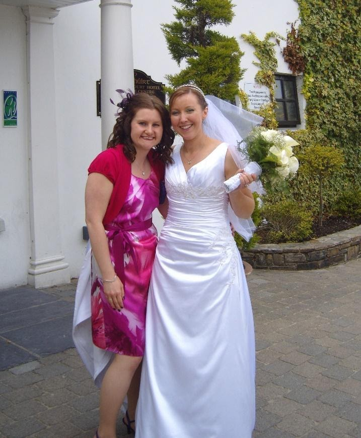 Lady in a pink and white dress stands next to a bride in a white dress.