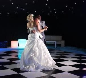 A bride and groom dance on a chequered dance floor. the groom is wearing a grey suit and the bride a strapless white dress.