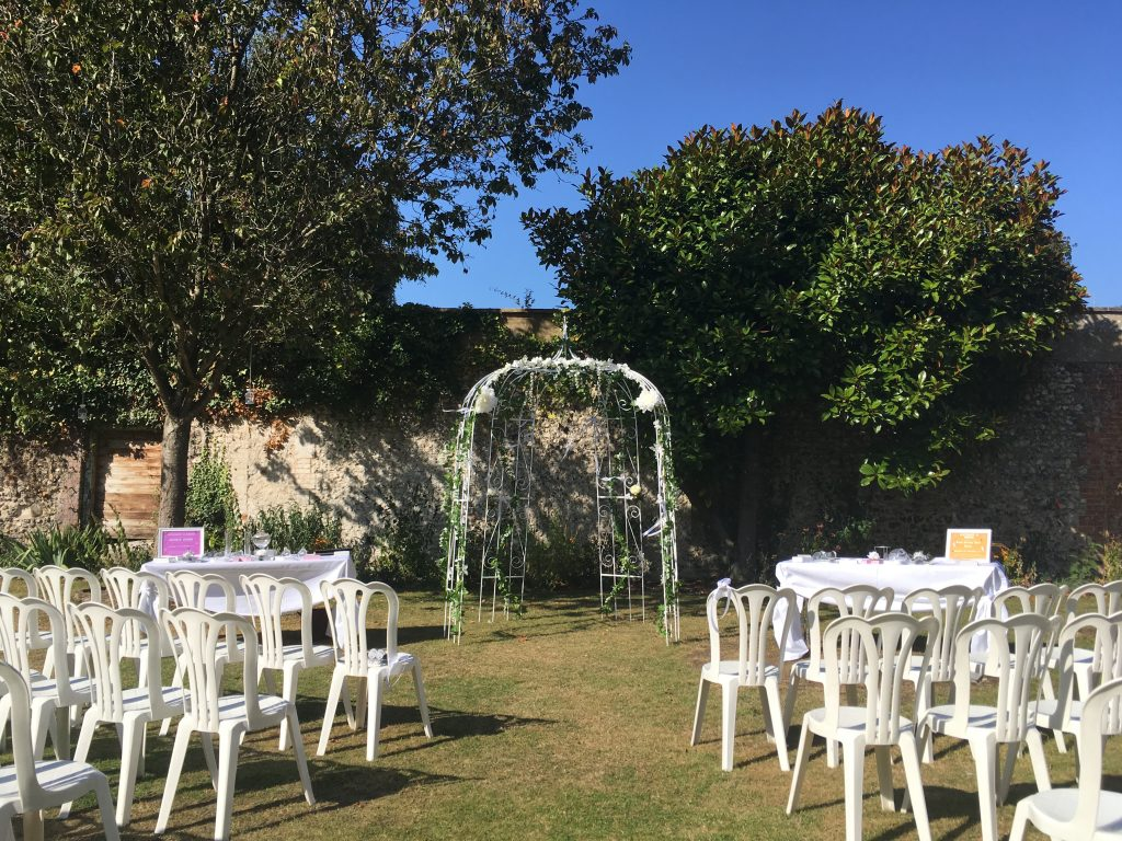 Outside ceremony set up. with chairs on either side of a arch.